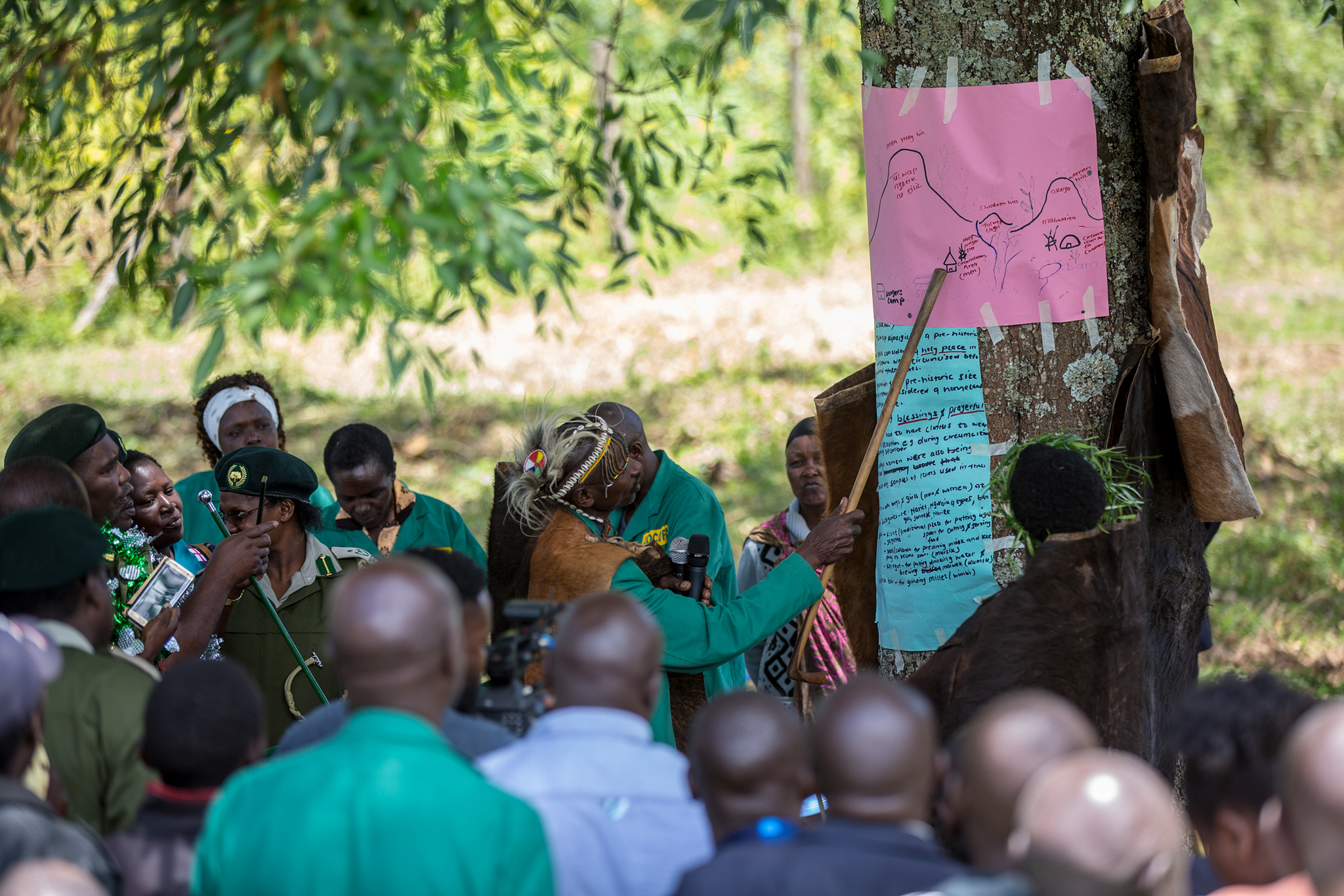 Community elder explaining the map of sacred hills in Londiani in Kenya's Rift Valley, on a tree to the community